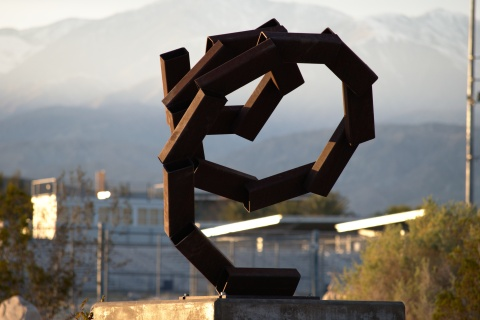 Spiral Shaped Sculpture with High School in Background